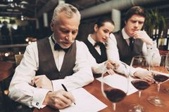 Two male sommeliers and female sommelier make up wine list sitting at table with glasses of wine. Confident sommelier tasting wine in restaurant stock image