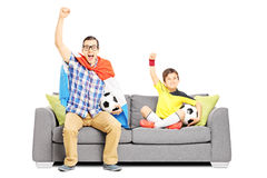 Two male sport fans seated on a sofa watching sport Royalty Free Stock Photography