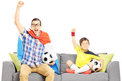 Two male sport fans sitting on a sofa and watching sport Stock Photo