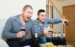 Two male sport fans watching game at home. Two excited male sport fans with beer watching hockey game heatedly at home Royalty Free Stock Images