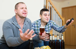 Two male sport fans watching game at home. Two excited male sport fans watching hockey game heatedly at home Royalty Free Stock Photography