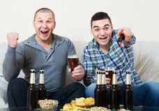 Two male sport fans watching game at home. Two happy male sport fans watching hockey game with beer heatedly at home Royalty Free Stock Images