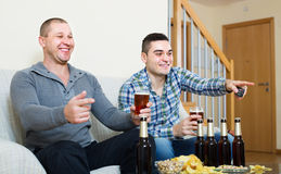 Two male sport fans watching game at home. Two happy male sport fans watching hockey game heatedly at home Royalty Free Stock Image