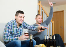Two male sport fans watching game at home Royalty Free Stock Image