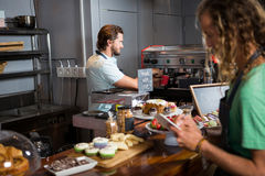 Two male staff working at counter. In coffee shop Stock Photography