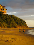 Two male surfers walk on wide beach carrying surfboards in Nicaragua at low tide Royalty Free Stock Photo