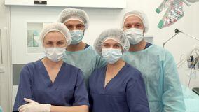 Two surgeons and two nurses pose at the surgery room stock image