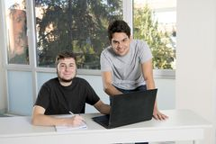 Teenager university students working on school classroom with la. Two male teenager university students working on school classroom with laptop computer together Royalty Free Stock Photography