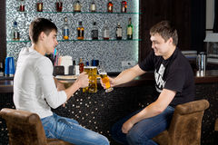 Two male teenagers sitting at the bar, toasting. Two happy male teenagers sitting at the bar holding glasses of beer, toasting, with shelves with bottles of Royalty Free Stock Image