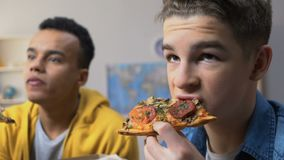 Two male teenagers watching tv and eating pizza, fatty cheap snacks, fast food