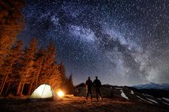 Two male tourists have a rest in the camping near the forest at night under night sky full of stars and milky way Stock Photo