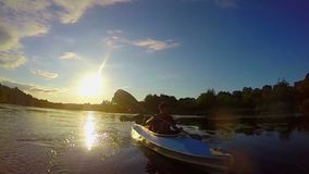 Two male tourists paddling kayak at sunset, beautiful landscape. Stock footage stock footage