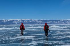 Two male tourists walk on frozen Baikal lake,Russia. Two male tourists in red jecket with hood walk on frozen Baikal lake to find the good spot to take photos at Royalty Free Stock Photo