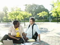 Two male university students sitting on ground with textbooks and laptop, smiling Stock Image