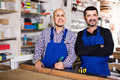 Two male woodworkers posing at workplace in workshop and smiling Royalty Free Stock Photography
