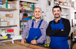 Two male woodworkers posing at workplace in workshop and smiling Stock Photo