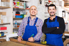 Two male woodworkers posing at workplace in workshop and smiling Stock Images