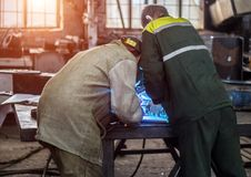 Two male workers at the factory welder and his assistant weld parts welding, sunset, workshop, welder stock photography