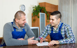Two male workers reading documents. Two smiling men in uniform reading contents of order at office royalty free stock image
