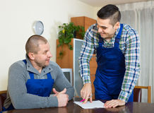 Two male workers reading documents Stock Image