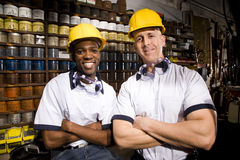 Two male workers wearing hard hats in storage room Royalty Free Stock Photo