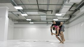Two male wrestlers in a white room work out throwing mats. Take a grapple and throw through yourself.  stock video