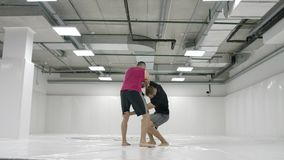 Two male wrestlers in a white room work out throwing mats. Take a grapple and throw through yourself.  stock footage