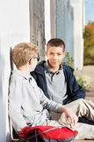 Two male youth friends sitting outside. Two teenage youth sitting against wall together outdoors after school Stock Image