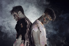 Two male zombies back to back on black smoky background Stock Photos
