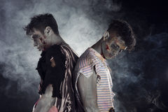 Two male zombies back to back on black smoky background Stock Photography