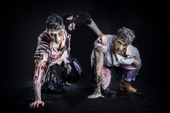 Two male zombies crawling on their knees, on black. Smoky background, looking at camera. Halloween theme Royalty Free Stock Photography