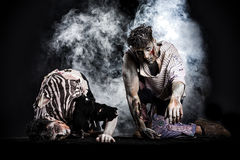 Two male zombies crawling on their knees, on black smoky background stock photo