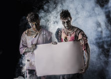 Two Male Zombies Holding Empty White Banner Royalty Free Stock Image