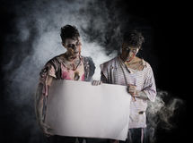 Two male zombies holding empty white banner Royalty Free Stock Images