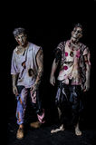 Two male zombies standing on black background Royalty Free Stock Images