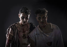 Two male zombies standing on black smoky background Royalty Free Stock Photos