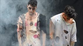 Two male zombies standing, moving on dark background background. Mostly looking at camera stock footage