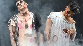 Two male zombies standing, moving on dark background background stock footage