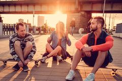 Two males and blond female sitting on longboards. Two males and blond female sitting on longboards in sunset time Stock Photos