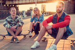 Two males and blond female sitting on longboards. Two males and blond female sitting on longboards in sunset time Royalty Free Stock Image