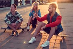 Two males and blond female sitting on longboards. Two males and blond female sitting on longboards in sunset time Stock Photo