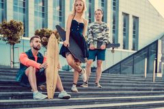 Two males and one female with longboards. Two males and one female with longboards posing on the street in urban style Royalty Free Stock Photography