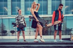 Two males and one female with longboards. Two males and one female with longboards posing on the street in urban style Royalty Free Stock Image