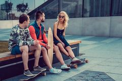 Two males and one female with longboards. Two males and one female with longboards posing on the street in urban style Royalty Free Stock Photo