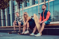 Two males and one female with longboards. Two males and one female with longboards posing on the street in urban style Royalty Free Stock Images