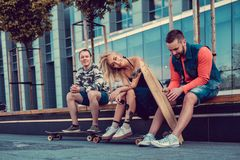 Two males and one female with longboards. Two males and one female with longboards posing on the street in urban style Stock Photos
