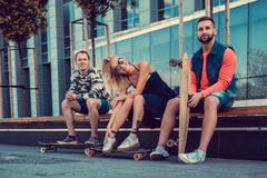 Two males and one female with longboards. Two males and one female with longboards posing on the street in urban style Stock Image