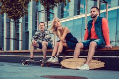 Two males and one female with longboards. Two males and one female with longboards posing on the street in urban style Royalty Free Stock Photos