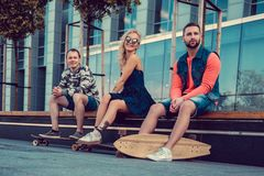 Two males and one female with longboards. Two males and one female with longboards posing on the street in urban style Stock Photography