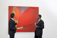 Two males talking over painting in art gallery Stock Images